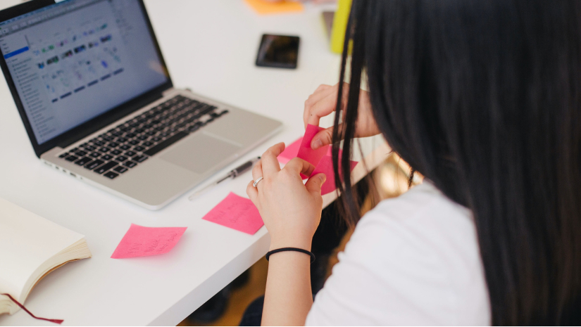 Woman writing things on post-it notes in an office
