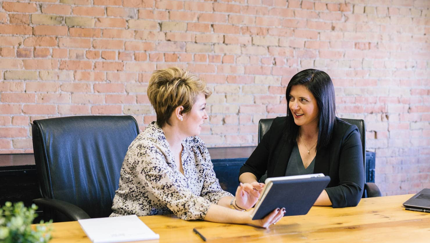 Two women discussing something at a conference table