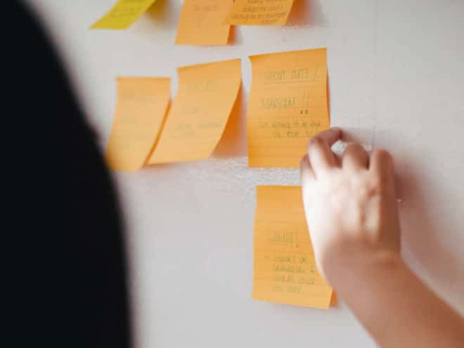 Person putting post-its on a board