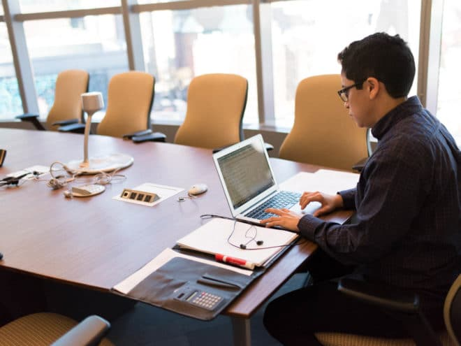 Man working on a laptop in a conference room