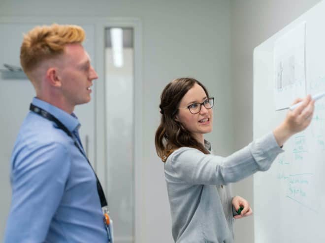 Woman showing man something on a white board