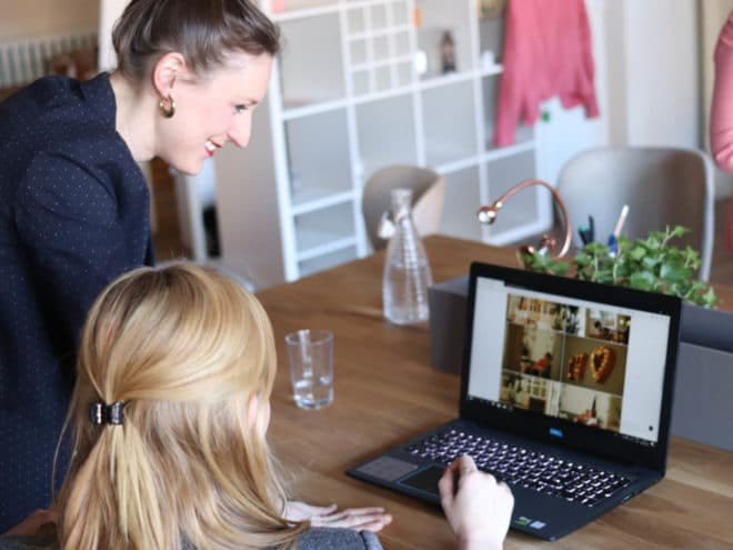 Woman helping other woman with something on the computer