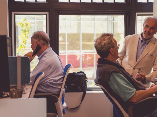 CIP group team members at their desks and talking