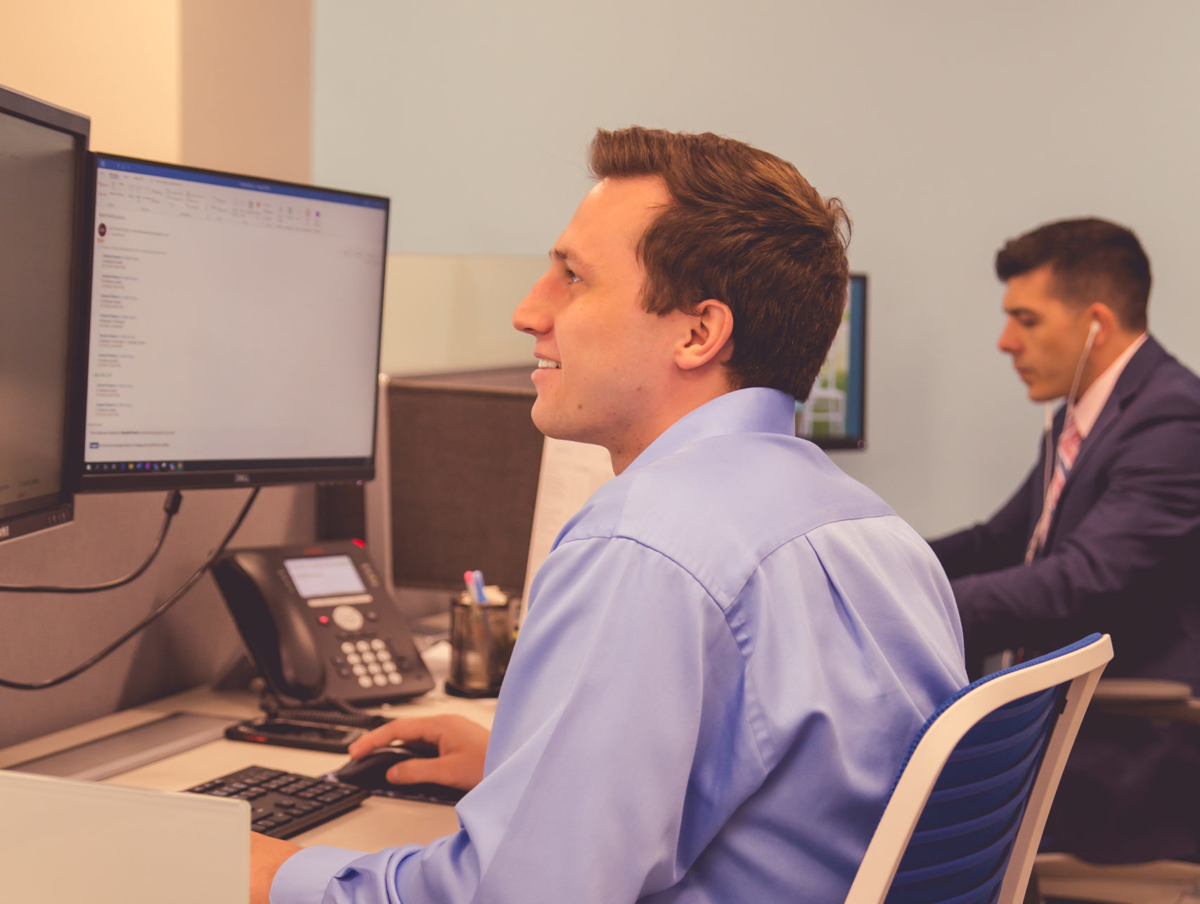Two male CIP Group team members sitting at their desks
